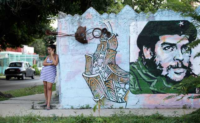 A young woman stands near mural of late revolutionary hero Che Guevara in Havana